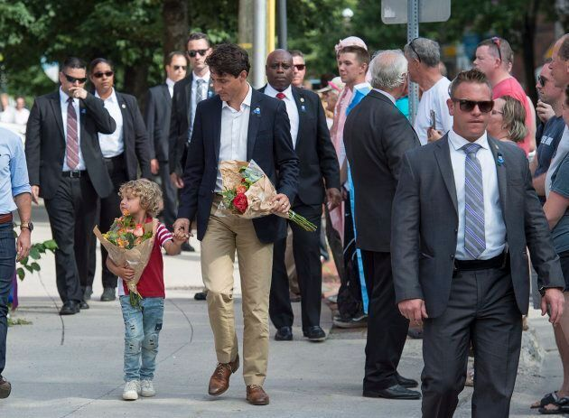 Prime Minister Justin Trudeau, accompanied by his four-year-old son Hadrien, walk to place flowers outside...