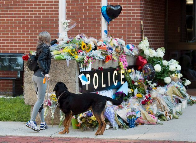 Flowers are placed on a makeshift memorial outside the police station in Fredericton on Saturday, Aug....