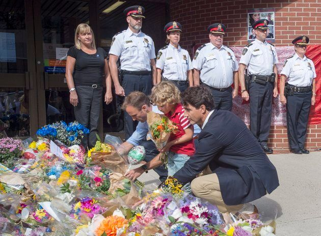 Prime Minister Justin Trudeau, accompanied by his four-year-old son Hadrien place flowers at a memorial...