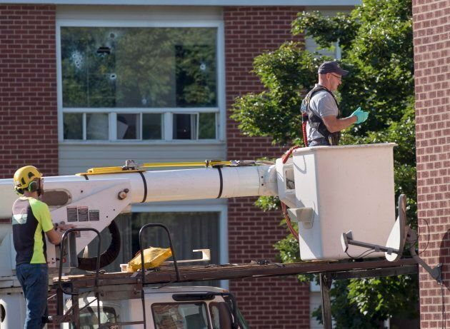 An RCMP forensic investigator examines a building adjacent to where Matthew Vincent Raymond is alleged...