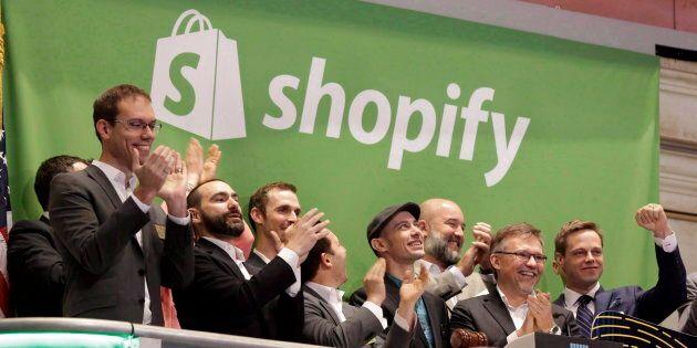 Shopify CEO Tobias Lutke, center wearing hat, rings the New York Stock Exchange opening bell, marking...