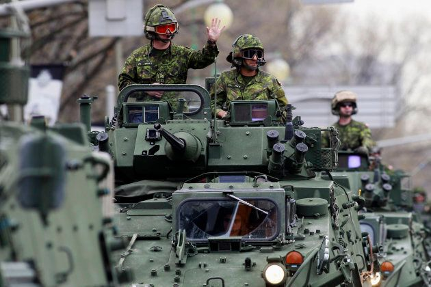 Members of the Canadian Armed Forces ride light armoured vehicles (LAV) to Parliament Hill during the National Day of Honour ceremony in Ottawa on May 9, 2014.