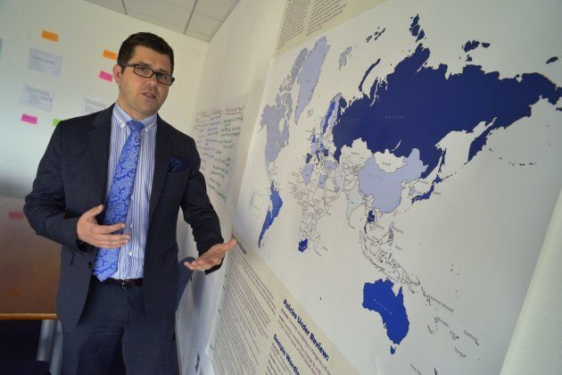 Jason Cianciotto, public policy director of nonprofit AIDS service organization Gay Men's Health Crisis, stands with a map showing international blood donation guidelines for men who have sex with men.