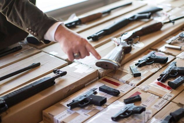 Police display guns seized during a series of raids for operation in Toronto on June 14,