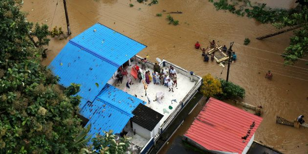 People wait for aid on the roof of their house at a flooded area in the southern state of Kerala, India,...
