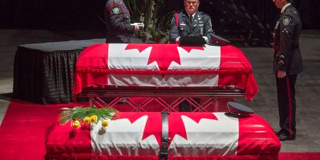 Members of the Fredericton Police Force place medals, hat and ceremonial belt on Constable Robb Costello's...