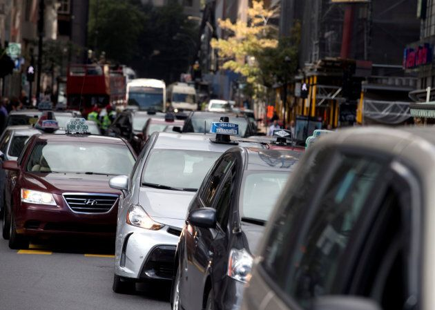 Taxis block the streets for their protest against Uber in Montreal on October 5,