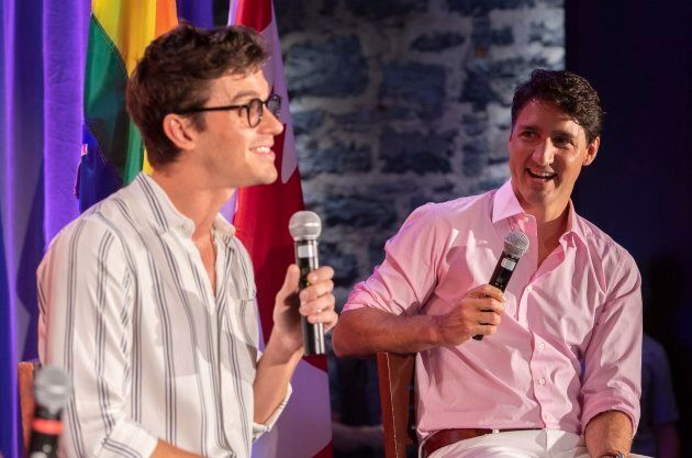 Prime Minister Justin Trudeau laughs as he listens to television personality Antoni Porowski during a party fundraiser in Montreal on Sunday, August 19, 2018.
