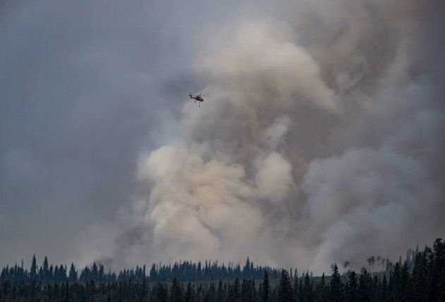 A helicopter fights a smaller fire near Fraser Lake, B.C., on August 15,