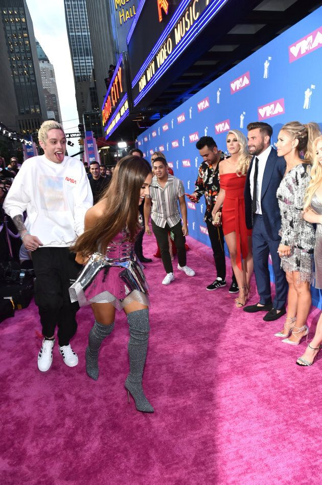 Pete Davidson and Ariana Grande walk past the cast of