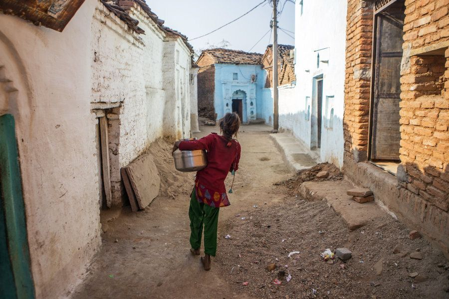A young woman carries a pot filled with water through the village of Shyampura in Tikamgarh, Madhya Pradesh,...