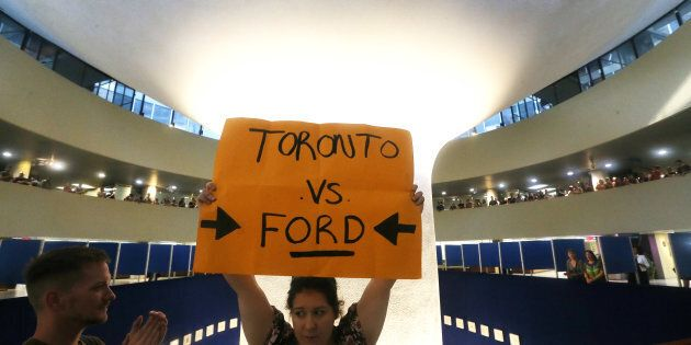 Protesters gather in the Toronto City Hall rotunda after an emergency motion pertaining to Premier Doug...