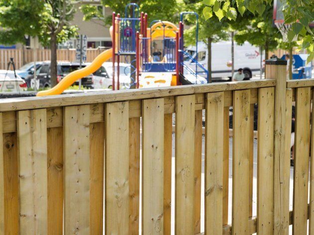 Police mark bullet holes in a fence where two young girls were shot at a playground in Scarborough, Ont.
