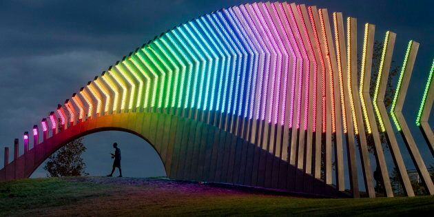 A man walks under Moving Surfaces, a giant steel and light sculpture at Ottawa's Lansdowne Park, as it is lit up in the colours of the rainbow, during Pride Week on Saturday.