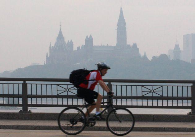 A cyclist make his way across a bridge into Ottawa as the Parliament buildings are seen through haze...