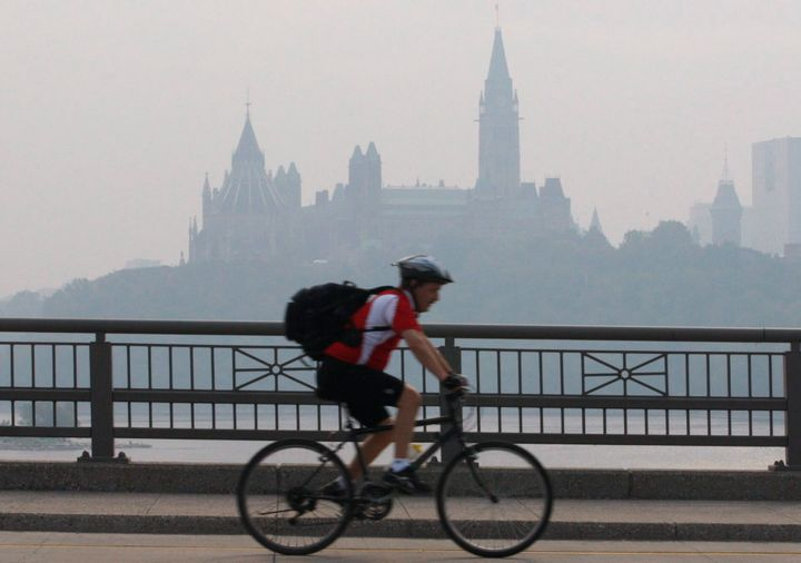 A cyclist make his way across a bridge into Ottawa as the Parliament buildings are seen through haze in Ottawa, Canada on May 31, 2010.