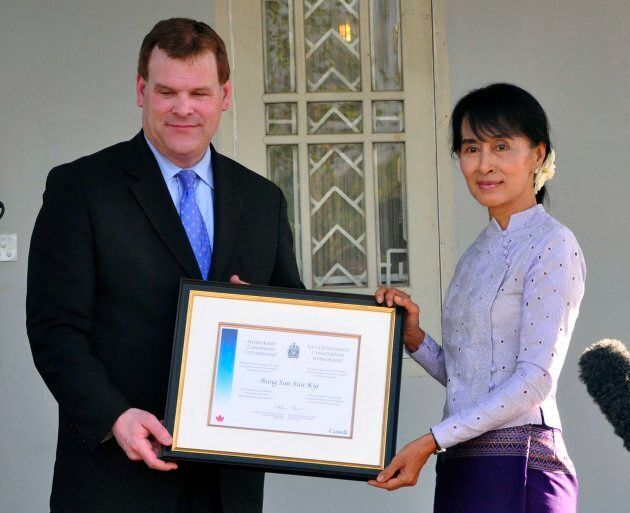 Former Canadian foreign affairs minister John Baird, left, presents an honorary Canadian citizenship certificate to Myanmar's democracy leader Aung San Suu Kyi during a press briefing after their meeting at her home on March 8, 2012, in Yangon, Myanmar.