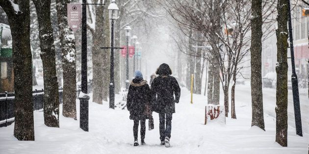 People walk down a street as large amounts of snow falls in Toronto, Dec. 11, 2014.