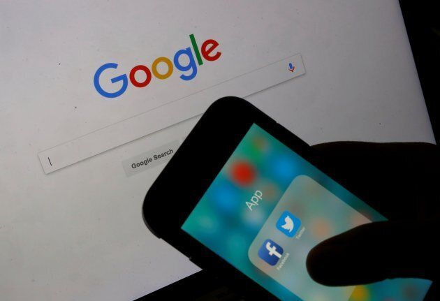 File photo of icons for the Facebook and Twitter applications are displayed on a smart phone in front of Google website.