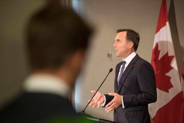 An aide looks on as federal Finance Minister Bill Morneau addresses journalists in Toronto on Aug. 30, 2018 about the government's Trans Mountain pipeline plan.
