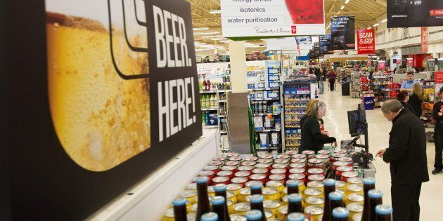 A man buys beer at a Loblaws grocery store in Kingston, Ont., Dec. 16, 2015. With the President's Choice...
