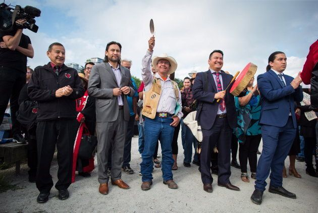 Coldwater Indian band Chief Lee Spahan, centre, raises an eagle feather before he and other First Nations...