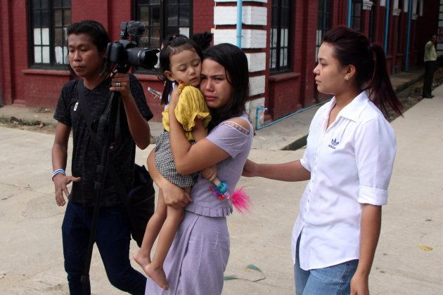 Reuters journalist Kyaw Soe Oo's wife, Chit Suu Win, and daughter, Moe Thin Wai Zan, leave the court...