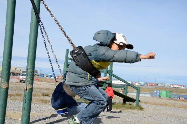 Inuit schoolchildren speak in English to each other on the playground at Leo Ussak Elementary School,...