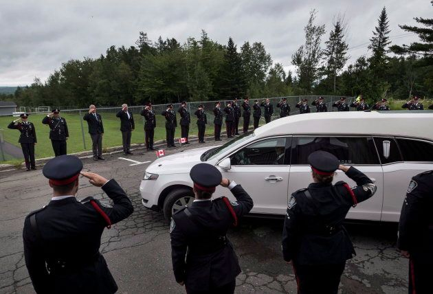 Fredericton police officers salute the hearse carrying slain colleague Const. Sara Burns on Aug. 18,