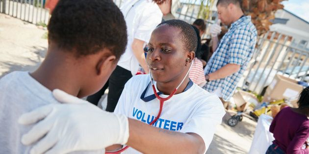Shot of a volunteer doctor examining a young patient with a