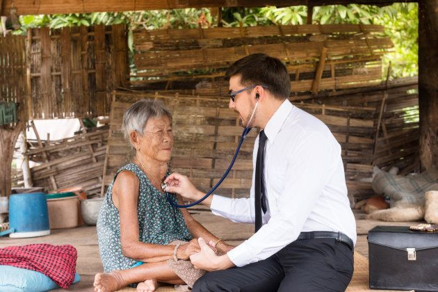 Doctor listening to a patient's heart beat and breathing in a rural