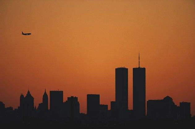 The sun sets at dusk over the Manhattan skyline silhouetting the Twin Towers of the World Trade Center.