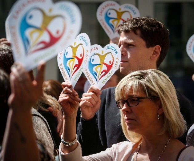 Family members of five slain students hold heart signs with their names on it following a court decision...