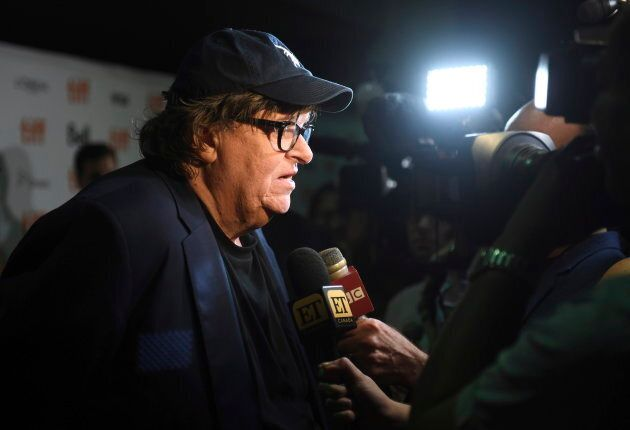 Michael Moore speaks with journalists as he attends the premiere of