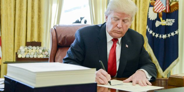 U.S. President Donald Trump signs a tax-overhaul bill into law in the Oval Office of the White House...