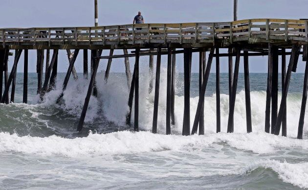 Waves crash under a pier in Kill Devil Hills, N.C. on Sept. 12, 2018, as Hurricane Florence approaches...