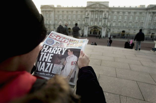 A man reads The Sun in front of Buckingham Palace on January 13, 2005 in London,