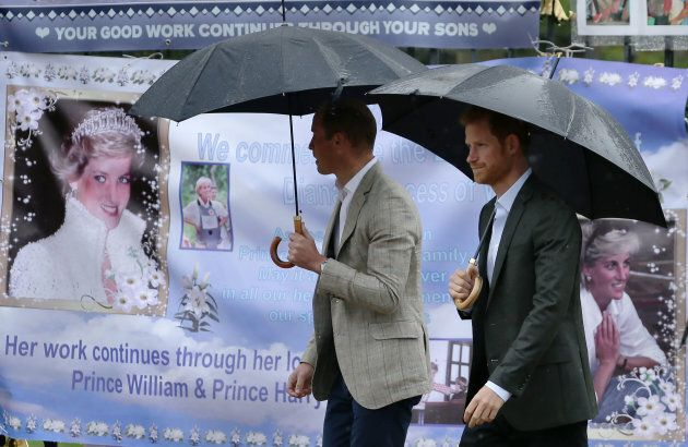 Prince William and Prince Harry look at tributes left by members of the public at one of the entrances...