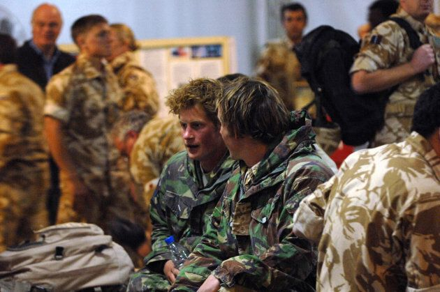Prince Harry talks with another officer at Kandahar air field on February 29,
