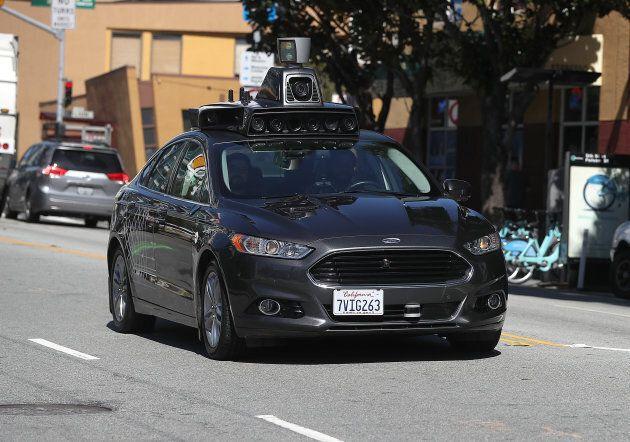 An Uber self-driving car drives down 5th Street in San