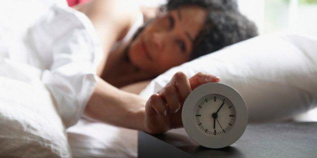 Black woman turning of alarm