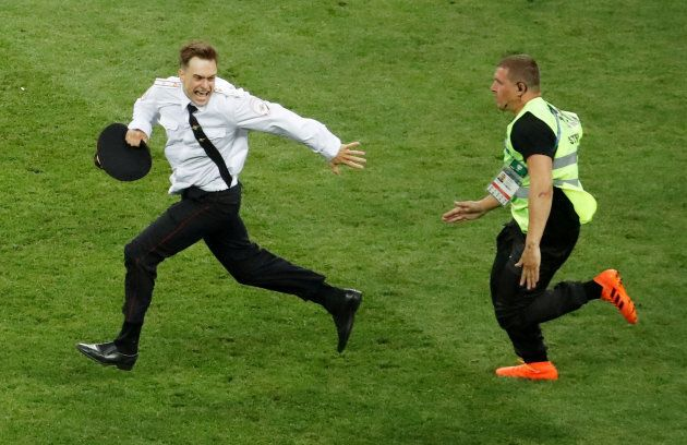 Pitch invader Pyotr Verzilov is chased by a steward during the