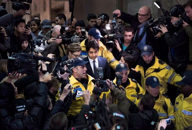 Jian Ghomeshi, centre, is escorted out of court after being released on bail in Toronto on on Nov. 26,