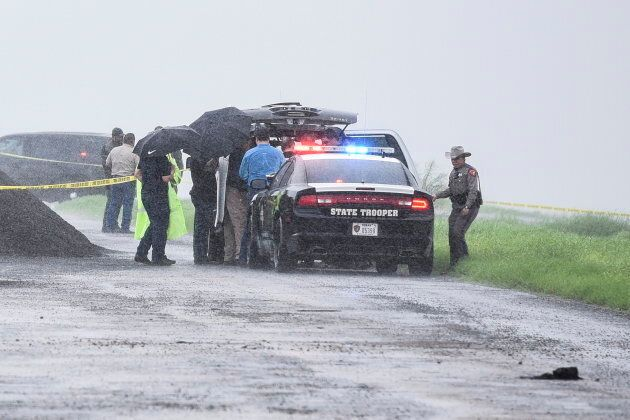 Law enforcement officers gather near the scene where the body of a woman was found near Interstate 35...
