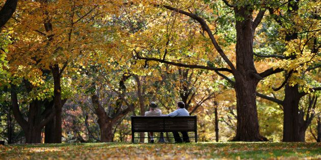 People sit on a bench on a warm autumn day at Rideau Hall in Ottawa, Oct. 23,