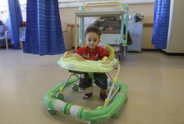 A boy sits in a baby walker in Benghazi, Libya, June 22, 2017. Walkers have been banned in Canada since
