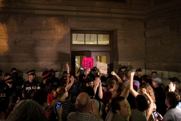 Police block a doorway as protesters demand entry to Queens Park after the public gallery was cleared and closed to onlookers as the Ontario legislature holds a midnight session to debate a bill that would cut the size of Toronto city council from 47 representatives to 25, in Toronto on Sept. 17, 2018.