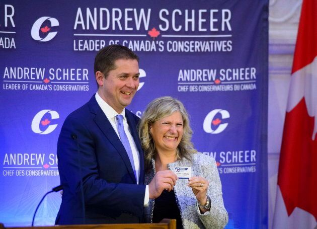 New Conservative MP Leona Alleslev is presented with a party card by Conservative Leader Andrew Scheer...