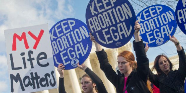 Pro-abortion rights supporters hold up signs in front of the Supreme Court in Washington, Thursday, Jan. 22, 2015, as they wait for the arrival of anti-abortion demonstrators during the annual March for Life. Thousands of anti-abortion demonstrators gathered in Washington for an annual march to protest the Supreme Court's landmark 1973 decision that declared a constitutional right to abortion. (AP Photo/Pablo Martinez Monsivais)