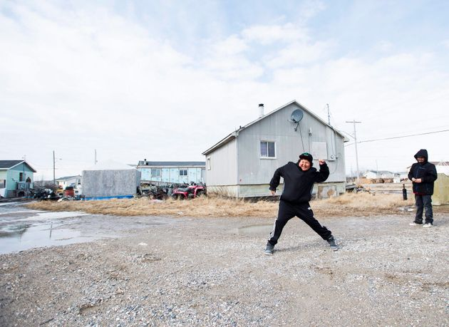 Teenage boys throw rocks in the northern Ontario First Nations reserve in Attawapiskat, Ont., on April...